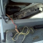 """Left """"cubby"""" in rear and access panel removed to show vehicle jack and trailer electrical connector."""