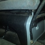View of bottom of drivers seat from rear showing installation  of additional 12VDC plug at base of seat.